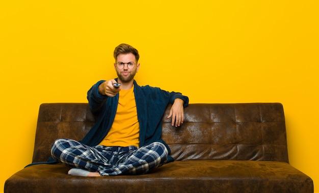 Tragende pyjamas des jungen mannes und sitzen auf einem sofa mit einer fernbedienung
