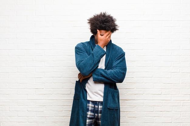 Tragende pyjamas des jungen schwarzen mannes mit dem kleid, das betont, beschämt oder gestört, mit kopfschmerzen, gesicht mit handbacksteinmauer bedeckend schaut