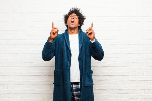Tragende pyjamas des jungen schwarzen mannes mit dem kleid, das ehrfürchtig und mit offenem mund aufwärts zeigend mit einem entsetzten und überraschten blick gegen ziegelstein glaubt