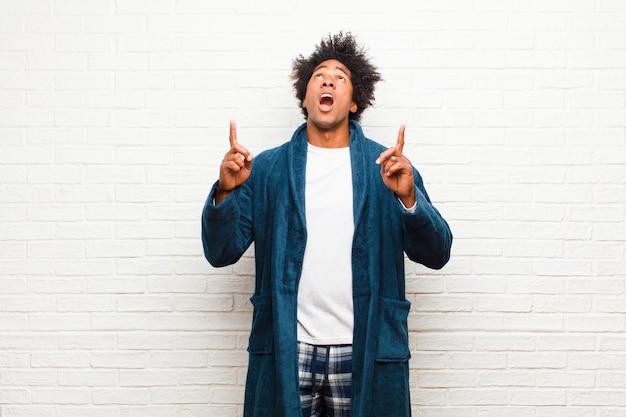 Tragende pyjamas des jungen schwarzen mannes mit dem kleid, das entsetzt, überrascht und mit offenem mund schaut und aufwärts mit beiden händen auf copyspace gegen ziegelstein zeigt