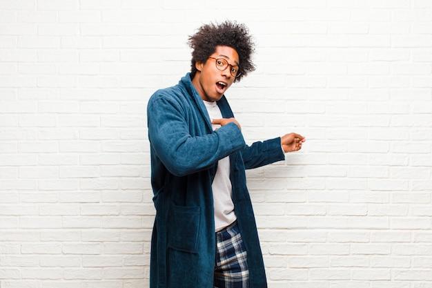 Tragende pyjamas des jungen schwarzen mannes mit dem kleid, das entsetzt und überrascht sich fühlt und auf copyspace auf der seite mit überraschtem, mit offenem mund blick gegen ziegelstein zeigt
