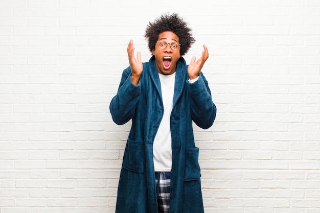 Tragende pyjamas des jungen schwarzen mannes mit dem kleid, das entsetztem und aufgeregtem lachen überrascht und glücklich wegen einer unerwarteten überraschung gegen backsteinmauer glaubt
