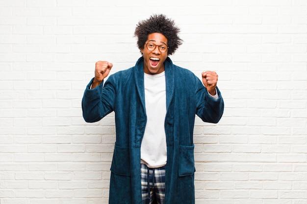 Tragende pyjamas des jungen schwarzen mannes mit dem kleid, das glücklich, positiv und erfolgreich sich fühlt und sieg, leistungen oder gutes glück gegen backsteinmauer feiert