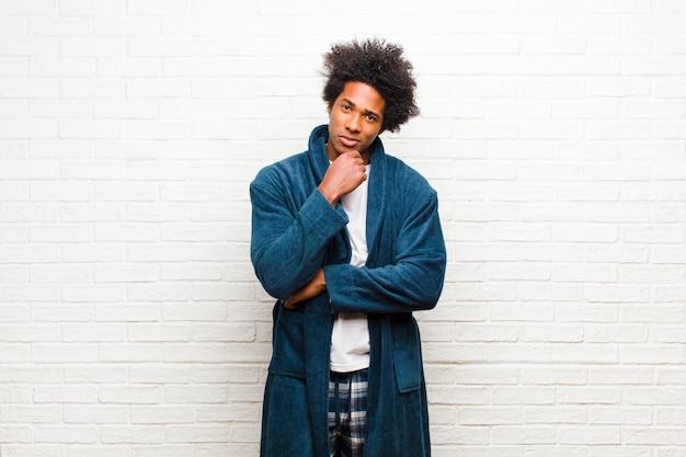 Tragende pyjamas des jungen schwarzen mannes mit dem kleid, das glücklich schaut und mit der hand auf kinn lächelt, eine frage sich wundert oder stellt und wahlen gegen ziegelstein vergleicht