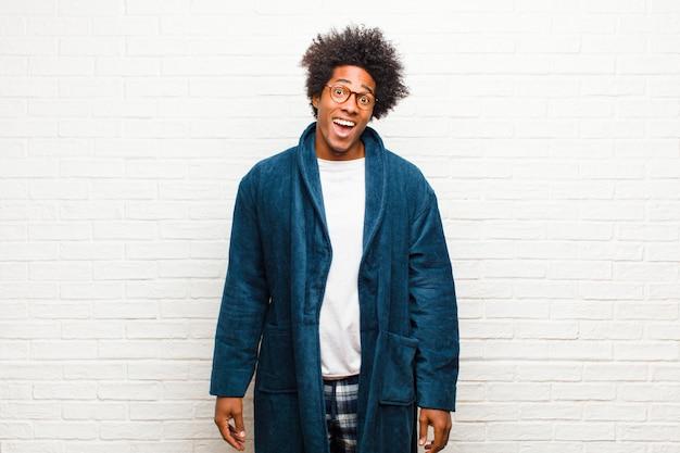 Tragende pyjamas des jungen schwarzen mannes mit dem kleid, das glücklich und angenehm überrascht aufgeregt mit einem faszinierten und entsetzten ausdruck gegen backsteinmauer schaut