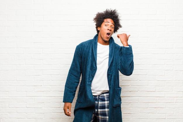 Tragende pyjamas des jungen schwarzen mannes mit dem kleid, das im unglauben erstaunt schaut, auf gegenstand auf der seite zeigt und wow, unglaublich gegen backsteinmauer sagt