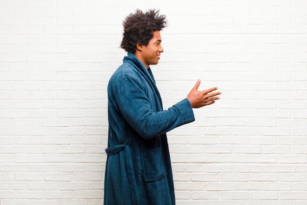 Tragende pyjamas des jungen schwarzen mannes mit dem kleid, das sie lächelt, grüßt und einen händedruck anbietet, um ein erfolgreiches abkommen, zusammenarbeitskonzept zu schließen