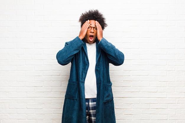 Tragende pyjamas des jungen schwarzen mannes mit dem kleid, das unangenehm entsetzt, erschrocken, der offene mund und das bedecken beider ohren mit handbacksteinmauer schaut
