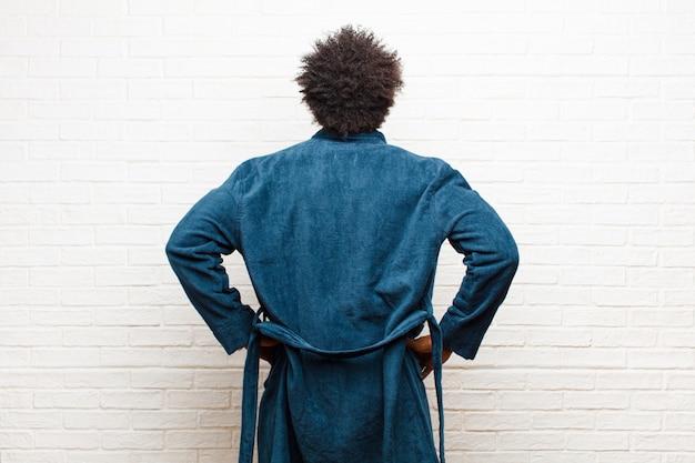 Tragende pyjamas des jungen schwarzen mannes mit dem kleid, das verwirrt oder voll oder zweifel und fragen, wundernd, mit den händen auf hüften, hintere ansicht glaubt