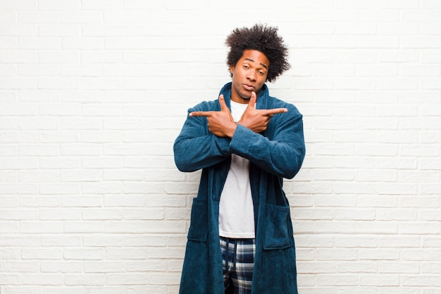 Tragende pyjamas des jungen schwarzen mannes mit dem kleid, das verwirrt und verwirrt, unsicher schaut und in entgegengesetzte richtungen mit zweifeln gegen backsteinmauer zeigt