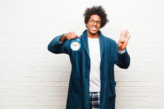 Tragende pyjamas des jungen schwarzen mannes mit einem wecker