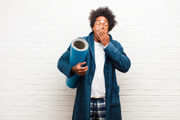 Tragende pyjamas des jungen schwarzen mannes mit einer yogamatte