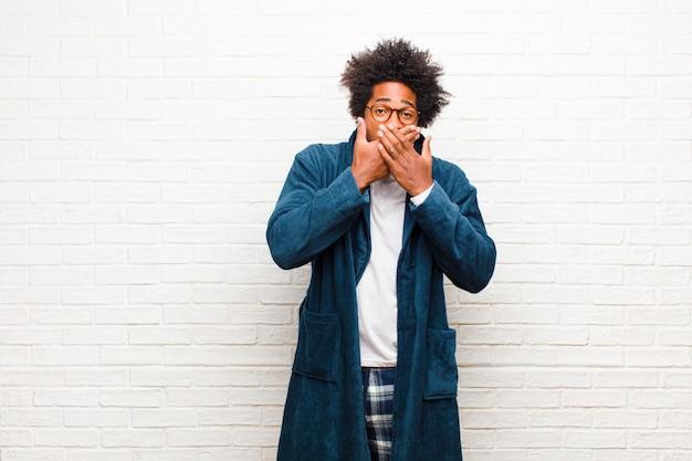 Tragende pyjamas des jungen schwarzen mannes mit kleiderbedeckungsmund mit den händen mit einem entsetzten, überraschten ausdruck, ein geheimnis halten oder ein oops gegen ziegelstein sagend