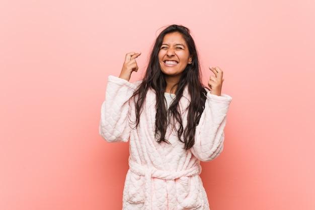 Tragende pyjamaüberfahrtfinger der jungen indischen frau für das haben des glücks