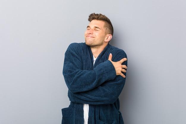 Tragende pyjamaumarmungen des jungen kaukasischen mannes, sorglos und glücklich lächelnd.