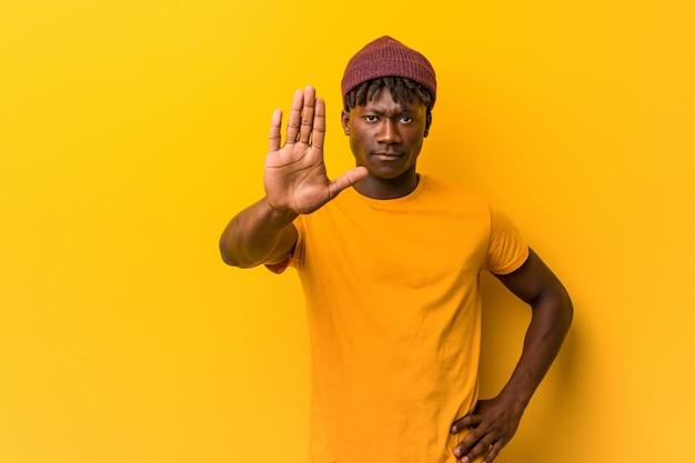 Tragende rastas des jungen schwarzen mannes über der gelben wand, die mit der ausgestreckten hand zeigt das stoppschild, sie verhindernd steht.