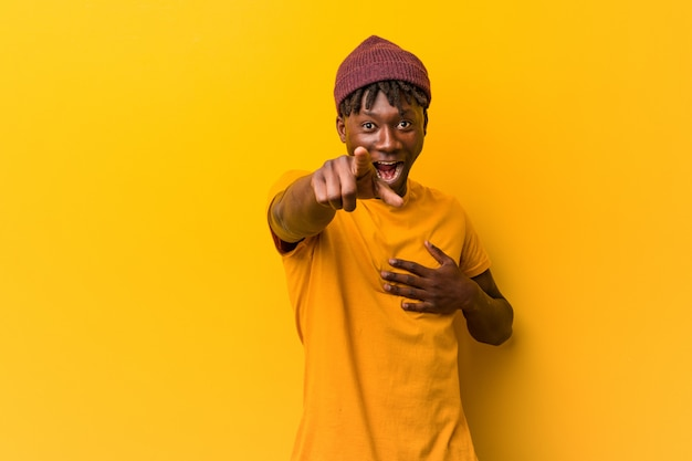 Tragende rastas des jungen schwarzen mannes über gelben punkten mit dem daumenfinger weg, lachend und sorglos.