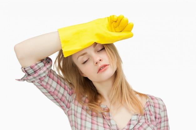 Tragende reinigungshandschuhe der frau beim abwischen ihrer braue