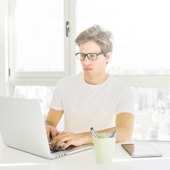 Tragende schauspiele des mannes, die zu hause an laptop arbeiten