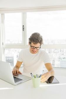 Tragende schauspiele des mittleren erwachsenen mannes, die laptop vor glasfenster verwenden
