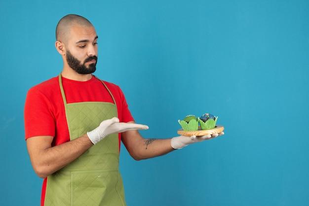 Tragende schürze des jungen gutaussehenden mannes, die kleine kuchen gegen blaue wand hält.