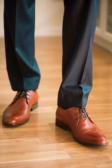 Tragende schuhe des mannes auf bretterboden. kleidungskonzept, bräutigam, der vor zeremonie fertig wird. körperdetail des geschäftsmannes.