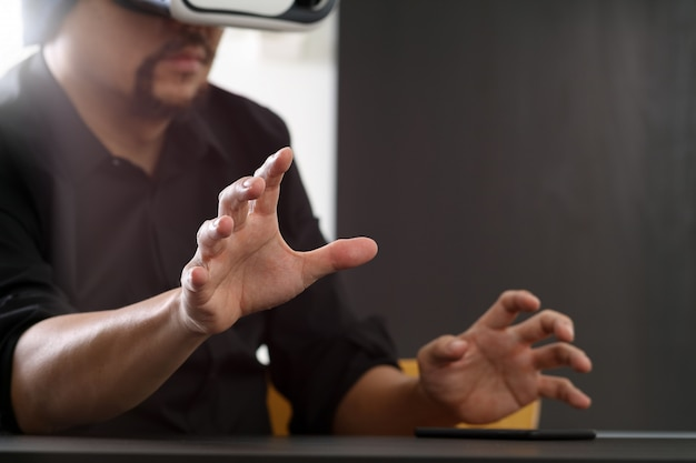 Tragende schutzbrillen der virtuellen realität des geschäftsmannes im modernen büro