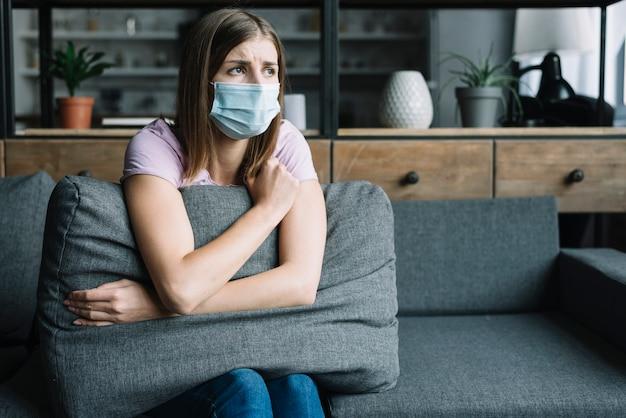 Tragende schutzmaske der frau, die auf sofa sitzt