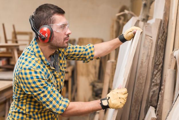 Tragende sicherheitsgläser des männlichen tischlers, die hölzerne planke in der werkstatt überprüfen