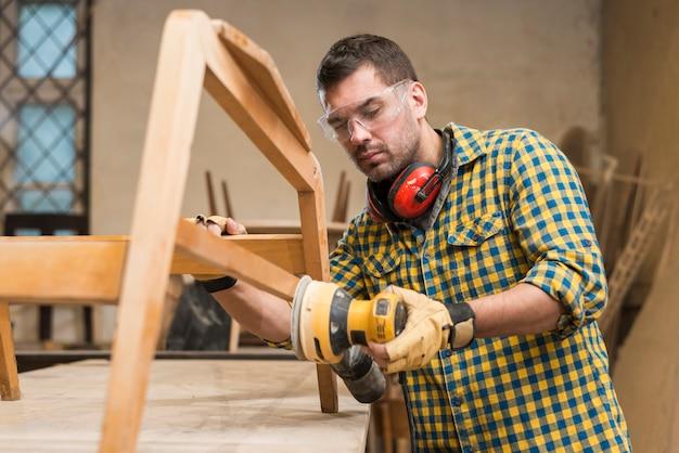 Tragende sicherheitsgläser eines männlichen tischlers unter verwendung der sandpapierschleifmaschine auf möbeln in der werkstatt
