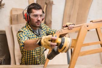 Tragende Sicherheitsgläser eines männlichen Tischlers und ein Ohrenschützer, die mit Sandpapierschleifmaschine auf Holzmöbeln arbeiten