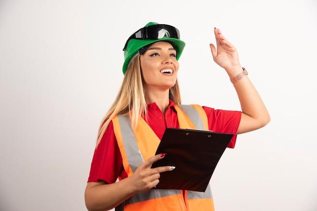 Tragende sicherheitsuniform und schutzbrillen der porträtarbeitskraftfrauenindustrie, die auf weißem hintergrund stehen.