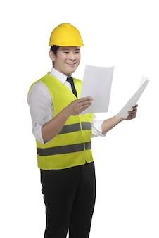Tragende sicherheitsweste der asiatischen arbeitskraft und gelber sturzhelm, der plan hält