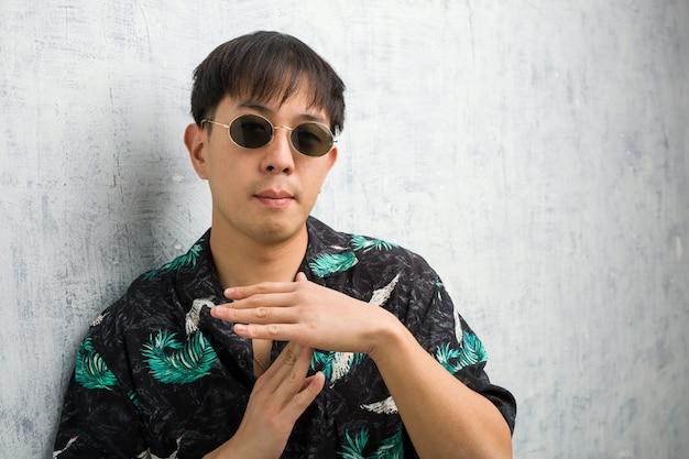 Tragende sommerausstattung des jungen chinesischen mannes, die eine auszeitgeste tut