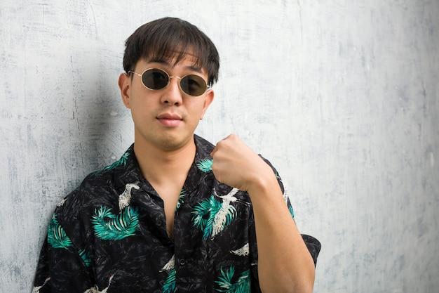 Tragende sommerausstattung des jungen chinesischen mannes, die finger, beispiel zeigt, um zu folgen