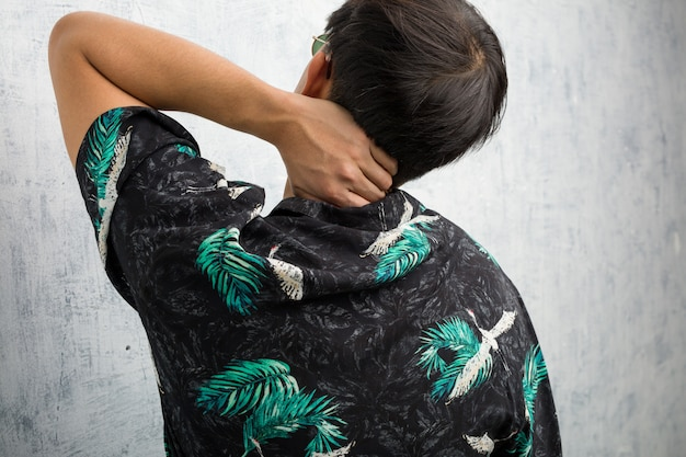 Tragende sommerausstattung des jungen chinesischen mannes von hinten denkend an etwas