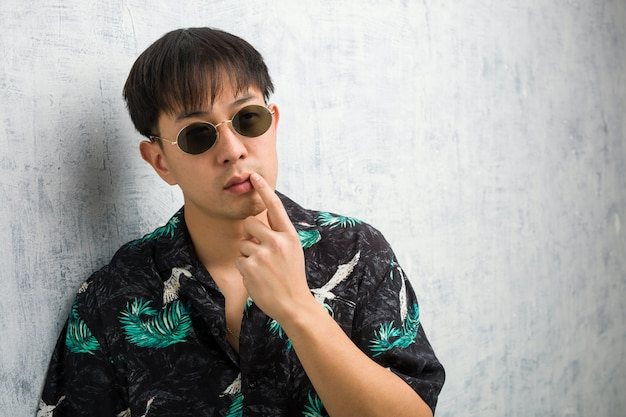 Tragende sommerausstattung des jungen chinesischen mannes zweifelhaft und verwirrt