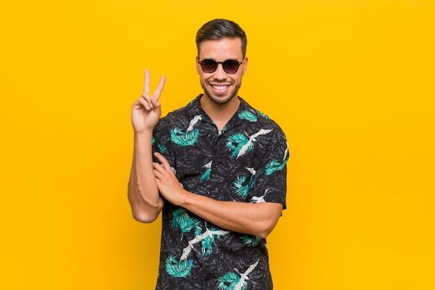 Tragende sommerkleidung des jungen philippinischen mannes, die nummer zwei mit den fingern zeigt.