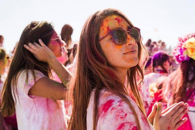 Tragende sonnenbrille der jungen frau verwirren mit holi farbe, die an der kamera looing ist
