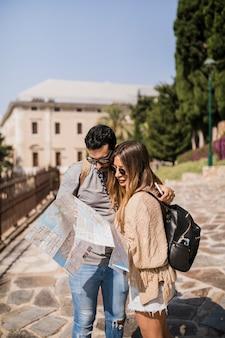 Tragende sonnenbrille der jungen paare touristische, die karte aufpasst