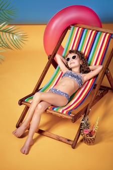 Tragende sonnenbrille und badeanzug des mädchens, die im regenbogenklappstuhl ein sonnenbad nehmen