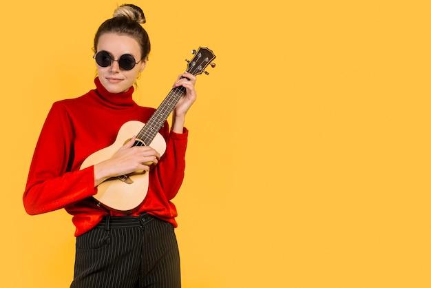 Tragende sonnenbrillen des mädchens, die das ukulele spielen