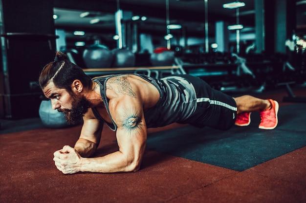 Tragende sportabnutzung des jungen mannes mit muskeln und handeln von plankenposition beim trainieren auf dem boden im dachbodeninnenraum