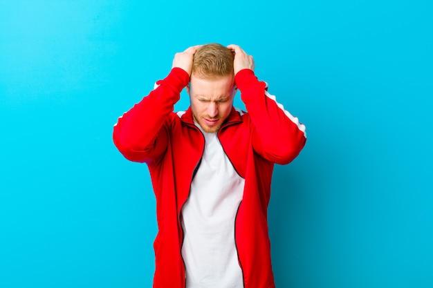 Tragende sportkleidung des jungen blonden mannes, die betont und frustriert sich fühlt, hände zum kopf anhebt, müde, unglücklich und mit migräne sich fühlt