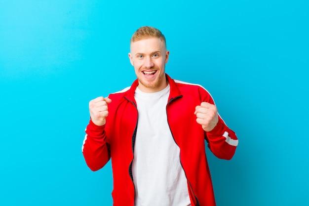 Tragende sportkleidung des jungen blonden mannes, die glücklich, positiv und erfolgreich sich fühlt und sieg, leistungen oder viel glück feiert