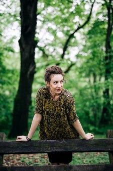 Tragende Strickjacke der jungen Frau und Aufstellung durch Holzbank im Park