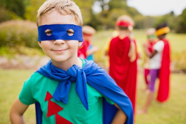Tragende superheld-kostümaufstellung des kleinen jungen