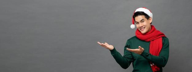 Tragende weihnachtskleidung des asiatischen mannes mit den armen hob auf graue fahne an