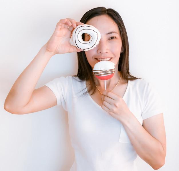 Tragende weiße hemden frauenasiens, die schaumgummiringe halten, um zu essen