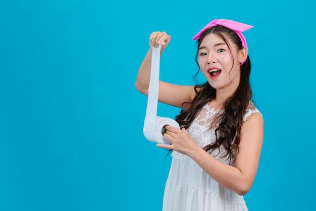 Tragende weiße pyjamas des mädchens, die ein seidenpapier in der hand auf dem blau halten.